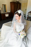 Όμορφη νέα νύφη με το makeup, τη φαντασία hairstyle στο άσπρο φόρεμα και τη συνεδρίαση πέπλων στο κρεβάτι που κοιτάζει προς Στοκ Εικόνα