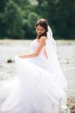 Όμορφη νέα νύφη πολυτέλειας στο μακρύ άσπρο γαμήλιο φόρεμα και πέπλο που στέκεται κοντά στον ποταμό με τα βουνά στο υπόβαθρο Στοκ Φωτογραφία
