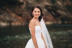 Όμορφη νέα νύφη πολυτέλειας στο μακρύ άσπρο γαμήλιο φόρεμα και πέπλο που στέκεται κοντά στον ποταμό με τα βουνά στο υπόβαθρο Στοκ φωτογραφία με δικαίωμα ελεύθερης χρήσης