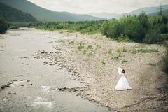 Όμορφη νέα νύφη πολυτέλειας στο μακρύ άσπρο γαμήλιο φόρεμα και πέπλο που στέκεται κοντά στον ποταμό με τα βουνά στο υπόβαθρο Στοκ φωτογραφίες με δικαίωμα ελεύθερης χρήσης