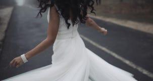 Όμορφη νέα νύφη στην άσπρη περιστροφή γαμήλιων φορεμάτων στο δρόμο, σε αργή κίνηση 4K απόθεμα βίντεο