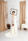 Όμορφη νέα νύφη στο γαμήλιο φόρεμα σαμπάνιας Στοκ Εικόνες