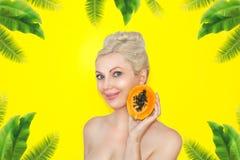 Όμορφη νέα ξανθή γυναίκα με papaya στα χέρια Η έννοια του υγιούς δέρματος και της ενυδάτωσης Πλεονεκτήματα των φρούτων στοκ φωτογραφία με δικαίωμα ελεύθερης χρήσης