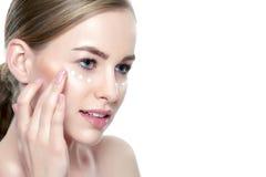 Όμορφη νέα ξανθή γυναίκα που εφαρμόζει την κρέμα προσώπου κάτω από τα μάτια της Του προσώπου επεξεργασία Cosmetology, ομορφιά και στοκ φωτογραφία με δικαίωμα ελεύθερης χρήσης