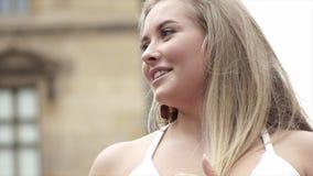 Όμορφη νέα ξανθή γυναίκα που χαμογελά στο υπόβαθρο της οικοδόμησης r Η ελκυστική νέα γυναίκα χαμογελά ευτυχώς να κοιτάξει στοκ φωτογραφίες με δικαίωμα ελεύθερης χρήσης