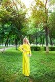 Όμορφη νέα ξανθή γυναίκα σε ένα φόρεμα υπαίθριο στοκ εικόνα