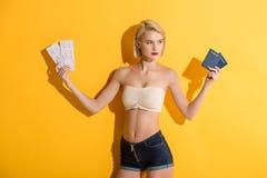 όμορφη νέα ξανθή γυναίκα στα σορτς τζιν και τα τοπ διαβατήρια και τα εισιτήρια εκμετάλλευσης Στοκ Φωτογραφίες