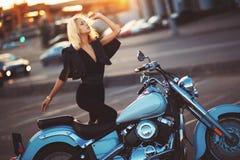 Όμορφη νέα ξανθή στάση γυναικών κοντά σε μια μοτοσικλέτα στο β Στοκ Φωτογραφία