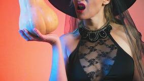 Όμορφη νέα προκλητική γυναίκα σε ένα μαύρα κοστούμι και ένα καπέλο μαγισσών, με μια κολοκύθα στα χέρια της διάστημα αντιγράφων 4k απόθεμα βίντεο