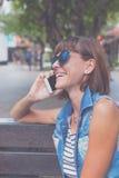 Όμορφη νέα προκλητική γυναίκα που χρησιμοποιεί τη συνεδρίαση smartphone σε έναν πάγκο στο πάρκο του Μπαλί όμορφη Ινδονησία νησιών Στοκ φωτογραφία με δικαίωμα ελεύθερης χρήσης