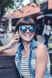 Όμορφη νέα προκλητική γυναίκα που χρησιμοποιεί τη συνεδρίαση smartphone σε έναν πάγκο στο πάρκο του Μπαλί όμορφη Ινδονησία νησιών Στοκ Εικόνες