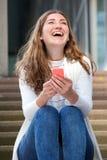 Όμορφη νέα συνεδρίαση γυναικών στα βήματα που γελούν με το κινητό τηλέφωνο Στοκ Εικόνα