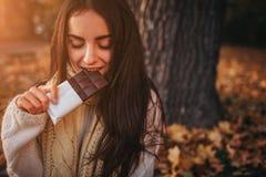 Όμορφη νέα συνεδρίαση brunette φύλλα ενός στα πεσμένα φθινοπώρου σε ένα πάρκο στοκ εικόνα με δικαίωμα ελεύθερης χρήσης