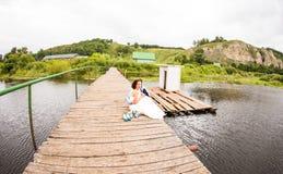 Όμορφη νέα συνεδρίαση γαμήλιων ζευγών στην αποβάθρα Στοκ Εικόνες