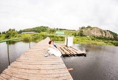 Όμορφη νέα συνεδρίαση γαμήλιων ζευγών στην αποβάθρα Στοκ εικόνα με δικαίωμα ελεύθερης χρήσης
