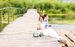 Όμορφη νέα συνεδρίαση γαμήλιων ζευγών στην αποβάθρα Στοκ φωτογραφία με δικαίωμα ελεύθερης χρήσης