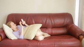 Όμορφη νέα συνεδρίαση γυναικών σε έναν καναπέ και παραγωγή ενός τηλεφωνήματος απόθεμα βίντεο