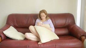 Όμορφη νέα συνεδρίαση γυναικών σε έναν καναπέ και παραγωγή ενός τηλεφωνήματος φιλμ μικρού μήκους