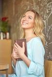 Όμορφη νέα συνεδρίαση γυναικών σε έναν πίνακα που κρατά ένα βιβλίο και ονειρεμένα που ανατρέχει Στοκ Εικόνες