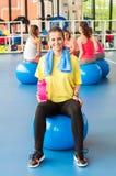 Όμορφη νέα συνεδρίαση γυναικών στην μπλε σφαίρα pilates και χαμόγελο Στοκ Εικόνες