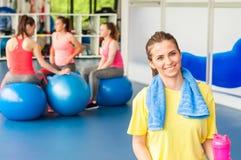 Όμορφη νέα συνεδρίαση γυναικών στην μπλε σφαίρα pilates και χαμόγελο Στοκ Φωτογραφία