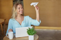 Όμορφη νέα συνεδρίαση γυναικών στον εργασιακό χώρο με το lap-top και τις ενάρξεις το αεροπλάνο εγγράφου Στοκ φωτογραφία με δικαίωμα ελεύθερης χρήσης