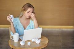 Όμορφη νέα συνεδρίαση γυναικών στον εργασιακό χώρο με το lap-top και κουρασμένος τσαλακώνοντας το φύλλο Στοκ φωτογραφίες με δικαίωμα ελεύθερης χρήσης