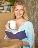 Όμορφη νέα συνεδρίαση γυναικών στον πίνακα, ανάγνωση ένα βιβλίο και εκμετάλλευση ένα φλυτζάνι του ποτού Στοκ φωτογραφία με δικαίωμα ελεύθερης χρήσης