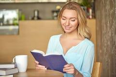 Όμορφη νέα συνεδρίαση γυναικών στον πίνακα και ανάγνωση ένα βιβλίο Στοκ Φωτογραφία