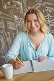 Όμορφη νέα συνεδρίαση γυναικών στον πίνακα και γράψιμο στο noteboo Στοκ φωτογραφίες με δικαίωμα ελεύθερης χρήσης