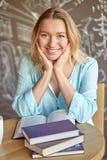 Όμορφη νέα συνεδρίαση γυναικών στον πίνακα με το ανοικτό βιβλίο στον καφέ Εκπαίδευση Στοκ Εικόνα