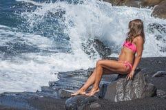 Όμορφη νέα συνεδρίαση γυναικών στο βράχο στοκ φωτογραφίες