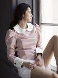 Όμορφη νέα συνεδρίαση γυναικών στο windowsill Στοκ Εικόνες