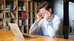 Όμορφη νέα τονισμένη συνεδρίαση επιχειρηματιών στο γραφείο του που χρησιμοποιεί το lap-top απόθεμα βίντεο