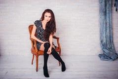 Όμορφη νέα τοποθέτηση γυναικών σε μια καρέκλα στοκ φωτογραφία