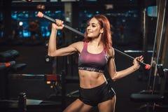 Όμορφη νέα τοποθέτηση κοριτσιών ικανότητας με τον αθλητικό εξοπλισμό στη γυμναστική τοποθέτηση με το barbell στοκ φωτογραφία με δικαίωμα ελεύθερης χρήσης
