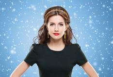 Όμορφη, νέα τοποθέτηση brunette με χρυσό headband και earrin Στοκ Φωτογραφίες