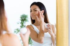 Όμορφη νέα φροντίδα γυναικών του δέρματός της που στέκεται κοντά στον καθρέφτη στο λουτρό στοκ φωτογραφία