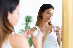 Όμορφη νέα φροντίδα γυναικών του δέρματός της που στέκεται κοντά στον καθρέφτη στο λουτρό στοκ φωτογραφία με δικαίωμα ελεύθερης χρήσης