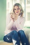 Όμορφη νέα χαλάρωση γυναικών με το φλυτζάνι του καυτού καφέ ή του τσαγιού Στοκ εικόνες με δικαίωμα ελεύθερης χρήσης