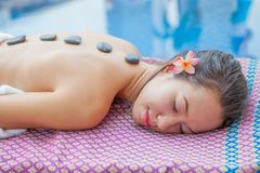 Όμορφη νέα χαλάρωση γυναικών σε ένα ξάπλωμα χ υγείας pool spa Στοκ Φωτογραφίες