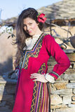 Όμορφη νέα χαμογελώντας γυναίκα με το βαλκανικό λαϊκό κόκκινο κοστούμι Στοκ Εικόνα