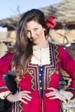 Όμορφη νέα χαμογελώντας γυναίκα με το βαλκανικό λαϊκό κόκκινο κοστούμι Στοκ Εικόνες