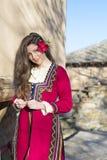 Όμορφη νέα χαμογελώντας γυναίκα με το βαλκανικό λαϊκό κόκκινο κοστούμι Στοκ Φωτογραφίες