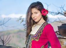 Όμορφη νέα χαμογελώντας γυναίκα με το βαλκανικό λαϊκό κόκκινο κοστούμι Στοκ εικόνες με δικαίωμα ελεύθερης χρήσης