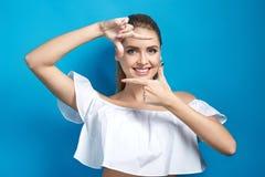 Όμορφη νέα χαμογελώντας γυναίκα που κάνει ένα πλαίσιο από τα χέρια της Στοκ Φωτογραφίες