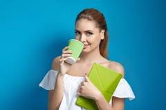 Όμορφη νέα χαμογελώντας γυναίκα που κρατά ένα σημειωματάριο και που πίνει ένα τσάι Στοκ φωτογραφίες με δικαίωμα ελεύθερης χρήσης