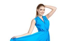 Όμορφη νέα χαμογελώντας γυναίκα που κρατά το μπλε φόρεμά της στο ελαφρύ υπόβαθρο Στοκ εικόνες με δικαίωμα ελεύθερης χρήσης