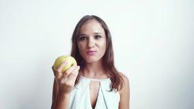 Όμορφη νέα χαρούμενη γυναίκα που τρώει τα πράσινα φρούτα μήλων η ανασκόπηση απομόνωσε το λευκό 3840x2160 απόθεμα βίντεο