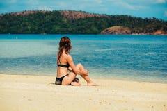 Όμορφη νέα χαλάρωση γυναικών στην τροπική παραλία Στοκ Φωτογραφίες